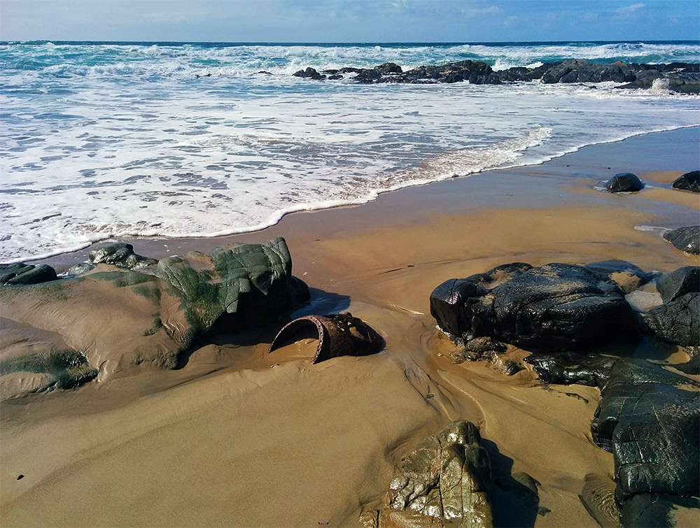 Picture of a wave rolling in on a sandy beach. An old mine/buoy in the sand between some rocks.