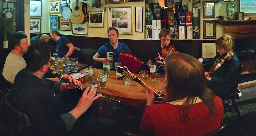 Picture of traditional musicians sitting around a table in a bar while playing