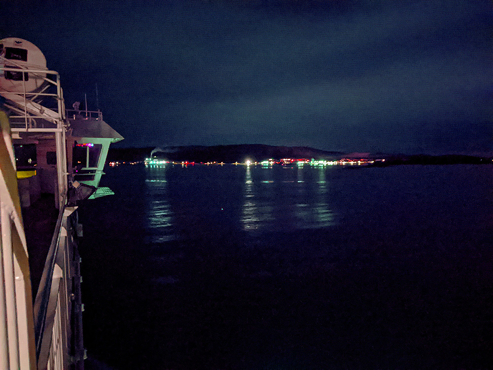 Picture of a view from the top deck of a ferry approaching a small harbour at night