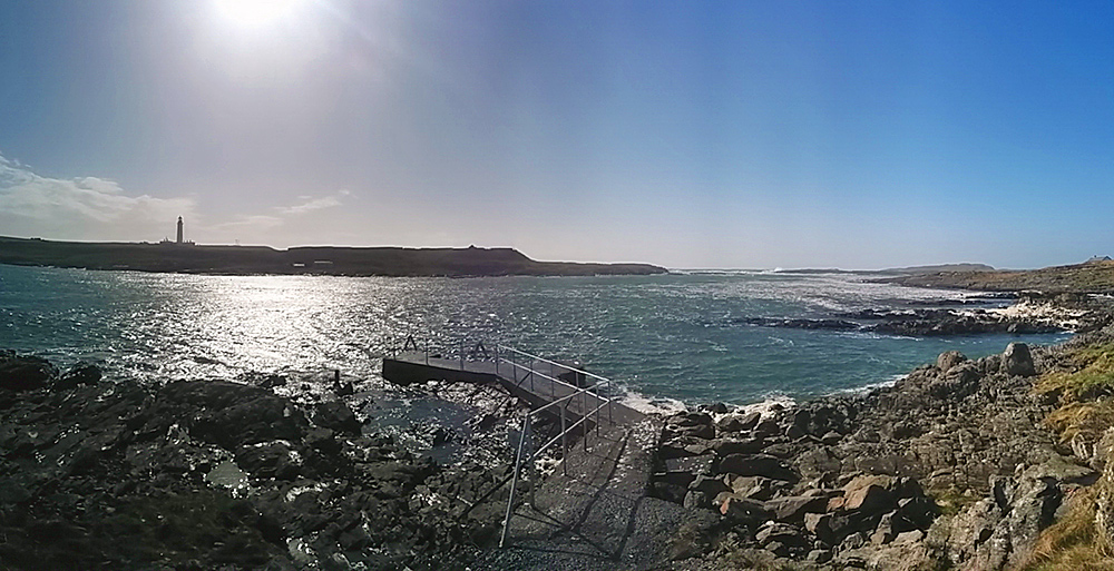 Panoramic picture of a small pier opposite a lighthouse on a small island