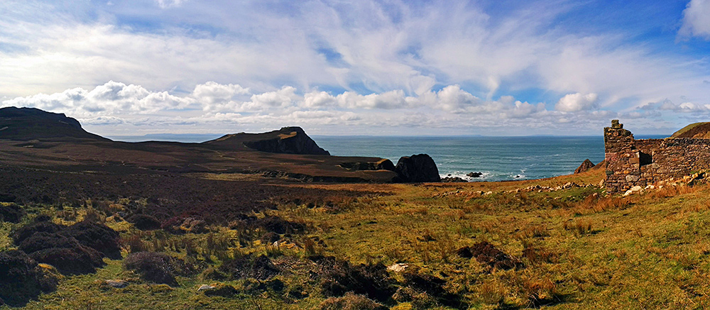 Panoramic picture of a hilly coastal landscape with cliffs and a ruin