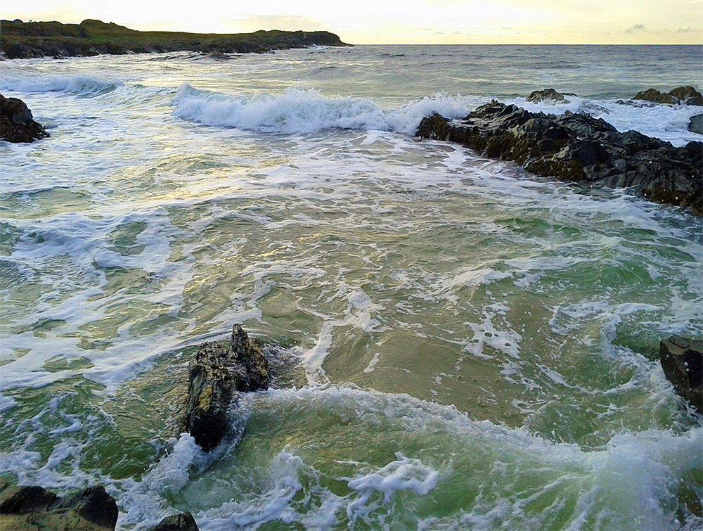 Picture of water rushing in at a rocky coast with sandy inlets