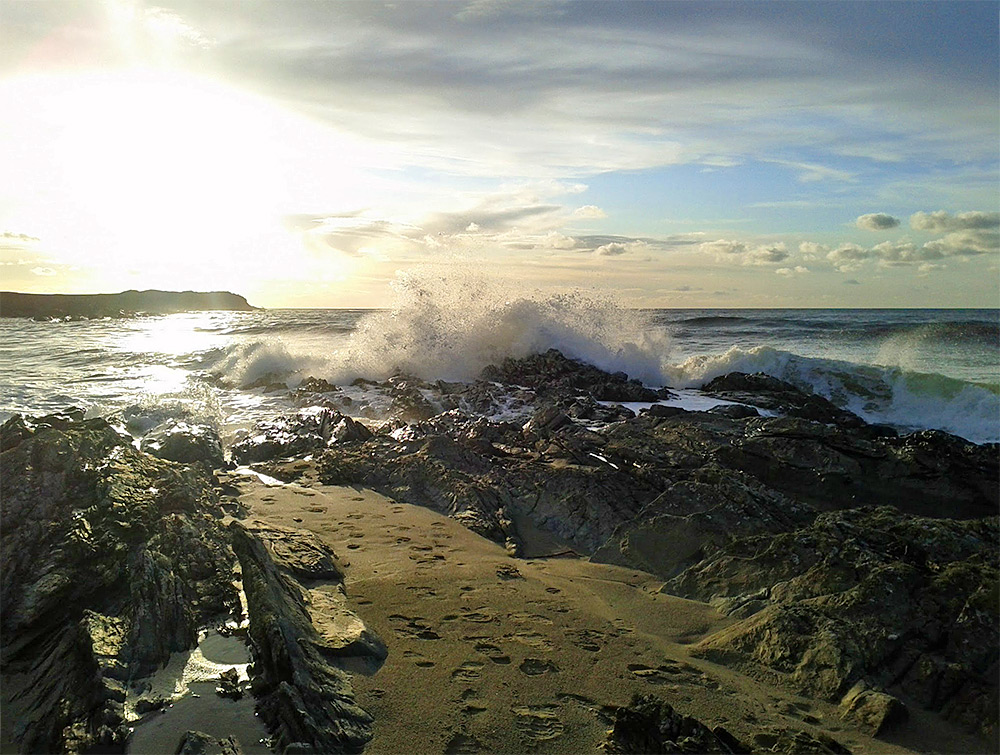 Picture of a wave breaking over rocks in a bay with rocks and beach along the coastline