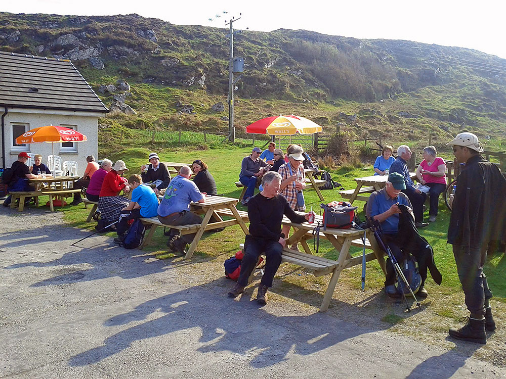 Picture of a group of walkers at the beer garden tables of a small restaurant on a sunny spring afternoon
