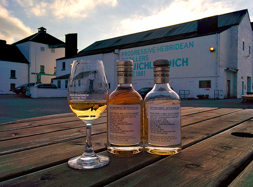 Picture of two small bottles of Bruichladdich samples and a glass on a wooden table in the evening sun at the distillery