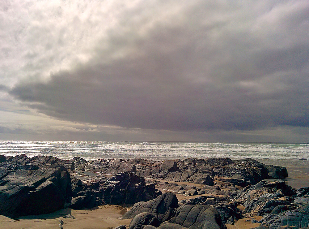 Picture of a bay with a beach and rocks under a heavy cloud but also bright light