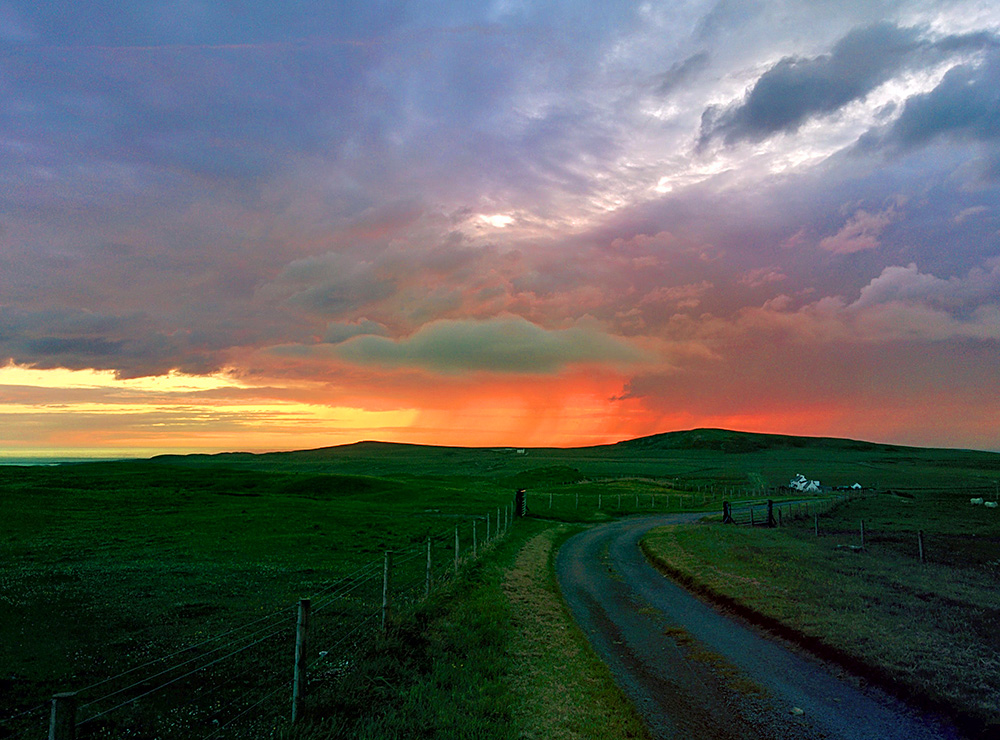 Picture of a colourful dramatic sunset seen from a hill behind another hill