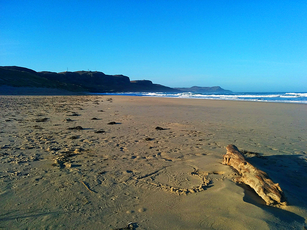 Picture of a beach with some driftwood and a heart drawn in the sand, taken on a sunny April morning
