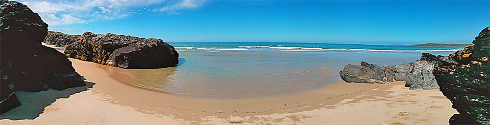 Panoramic picture of a beach with a few rocks, sand and water flowing in