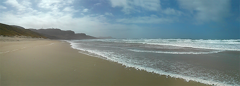 Panoramic picture of a sandy beach with waves rolling in from the Atlantic