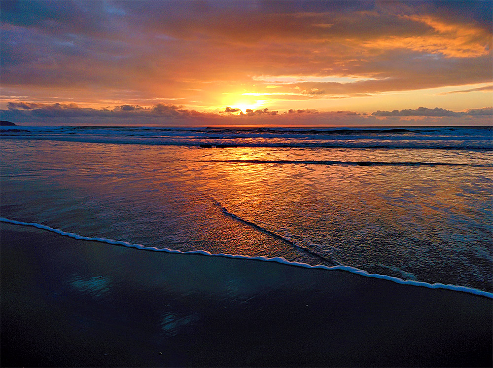 Picture of a colourful sunset over a bay with a sandy beach, a wave running out over the beach