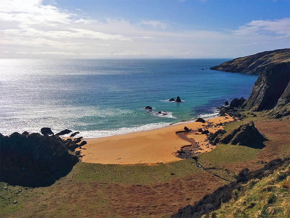 Picture of a small sandy beach in a cove on a sunny day