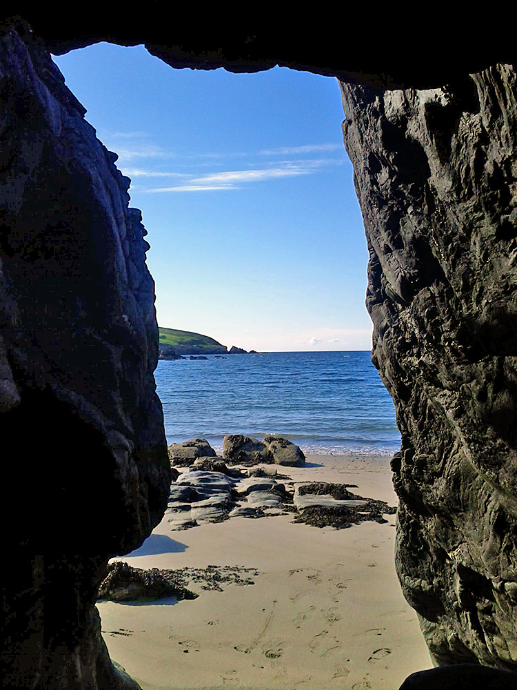 Picture of a view out from between rocks/small cave over a beach and a bay