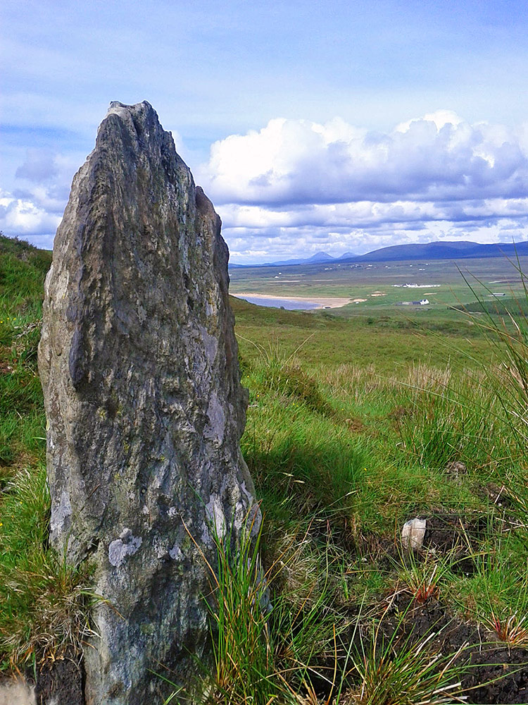 Picture of a small standing stone on a hill above a beach