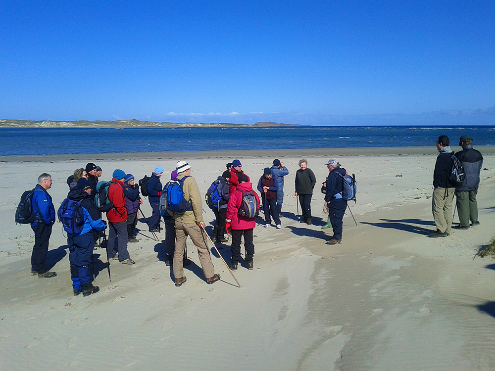Picture of a group of walkers listening to the walk leader telling a story on a beach