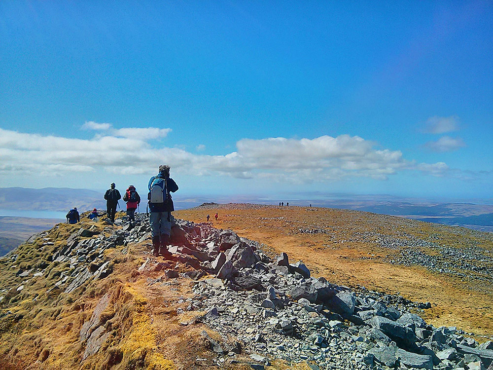 Picture of a group of walkers leaving the summit of a mountain
