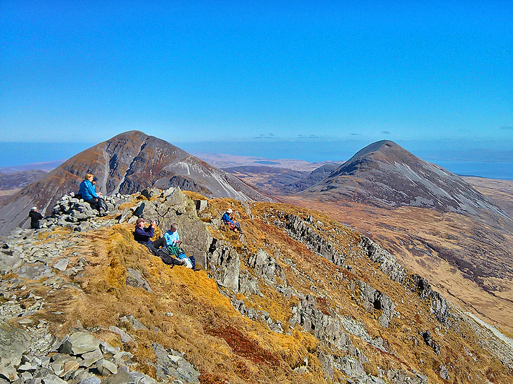 Picture of a group of walkers resting on the top of a mountain, two other mountains in the background