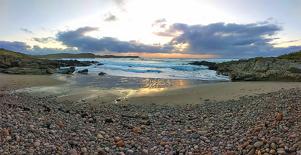 Panoramic picture of a sunset over a bay with a pebble and sand beach