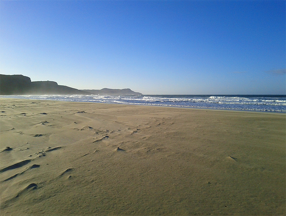 Picture of a bright sunny November morning at a wide bay with a sandy beach