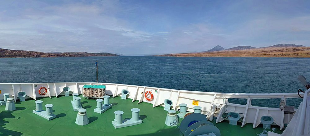 Panoramic picture from the bow of a ship cruising up a sound between two islands