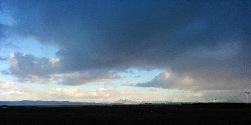 Picture of three distant mountains under dark clouds