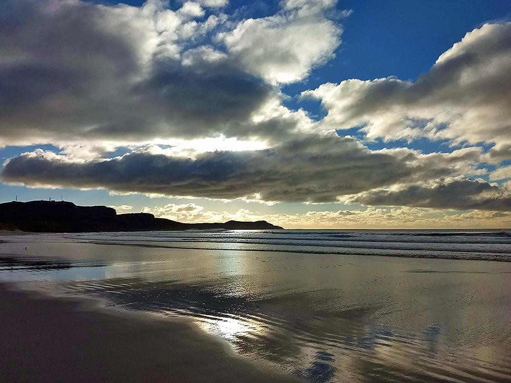 Picture of clouds with a few bright sunny breaks over a bay with a sandy beach