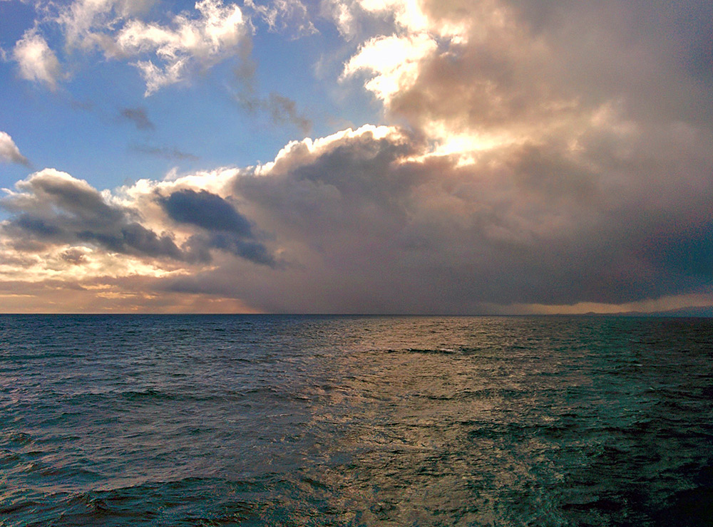 Picture of a dramatic cloud with a heavy rain shower over the sea off an island