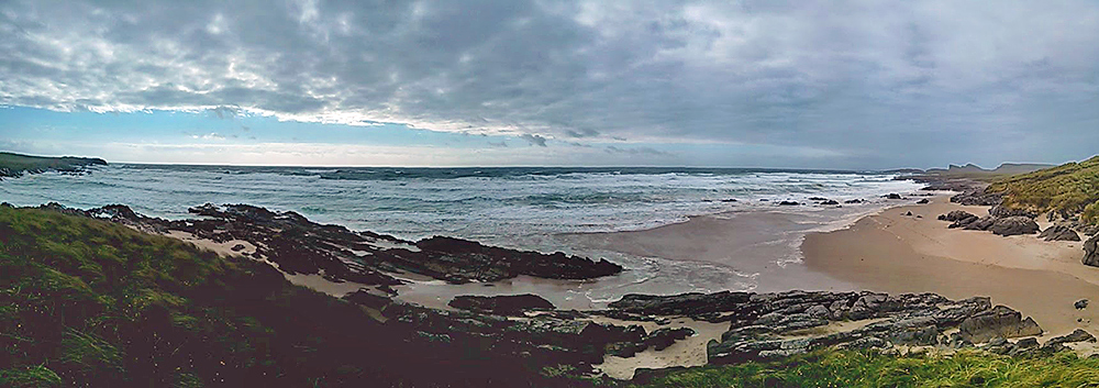 Panoramic picture of a bay with a beach under a cloudy moody sky