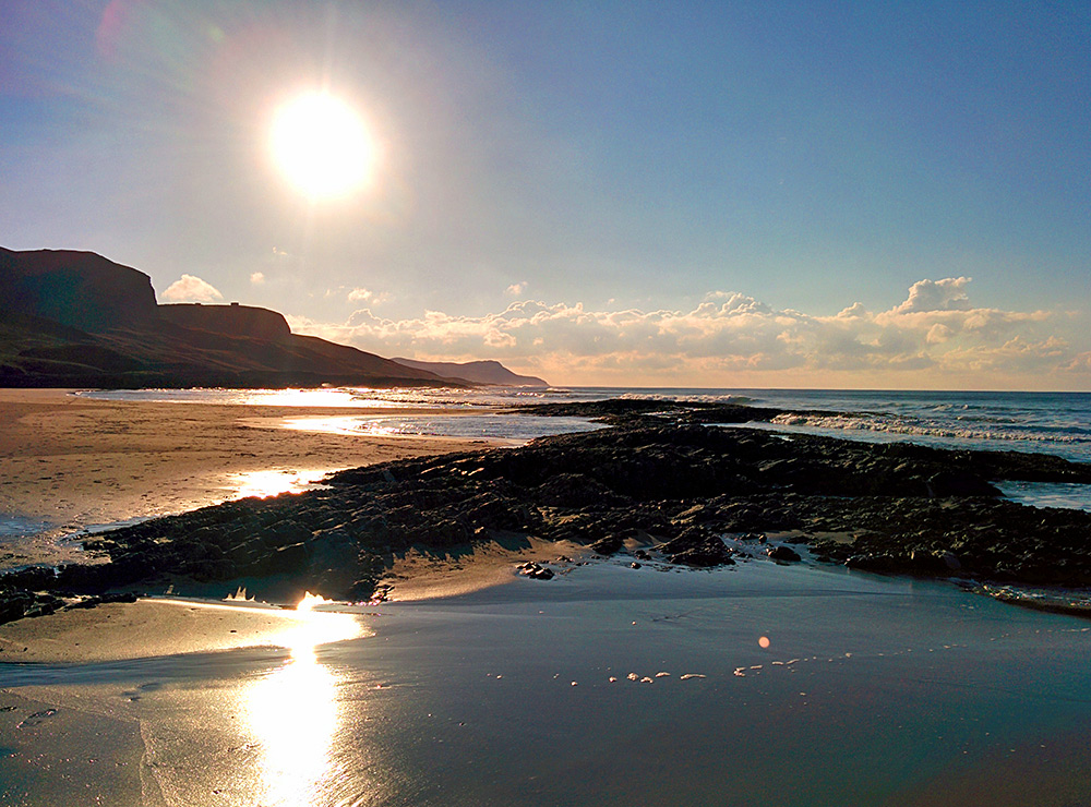 Picture of a low November sun over a bay with steep cliffs and a beach