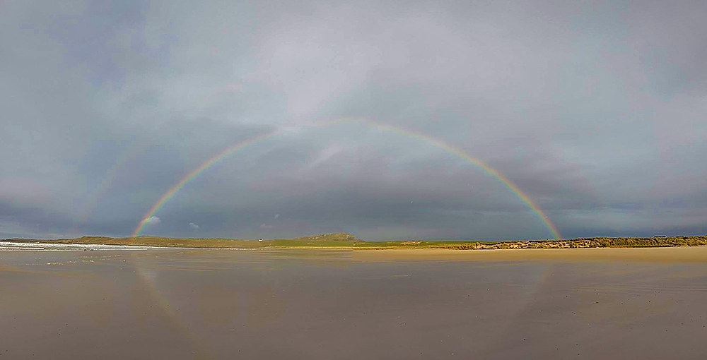 Panoramic picture of a rainbow over a farm and a hill, seen from a beach