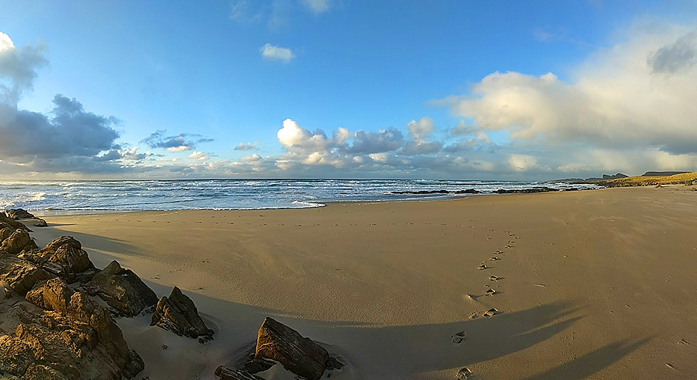 Panoramic picture of a sandy beach with waves rolling in from the Atlantic on a brisk November day