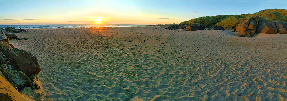 Panoramic picture of a sunset viewed from a churned up beach after a day with many visitors