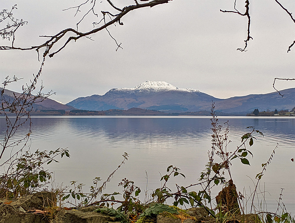 Picture of a mountain with a snow capped top seen across a lake