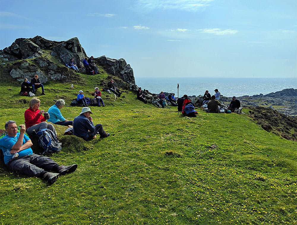 Picture of a group of walkers on their lunch break near a coast