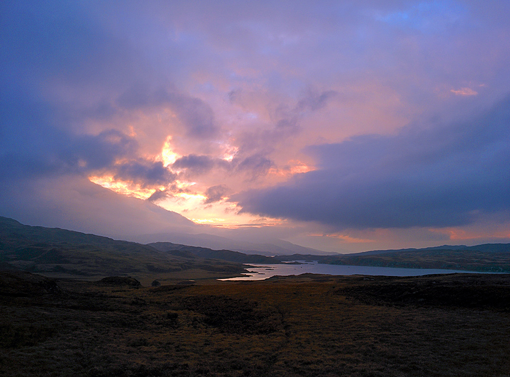 Picture of a sea loch in some dramatic evening light under a mostly cloudy sky