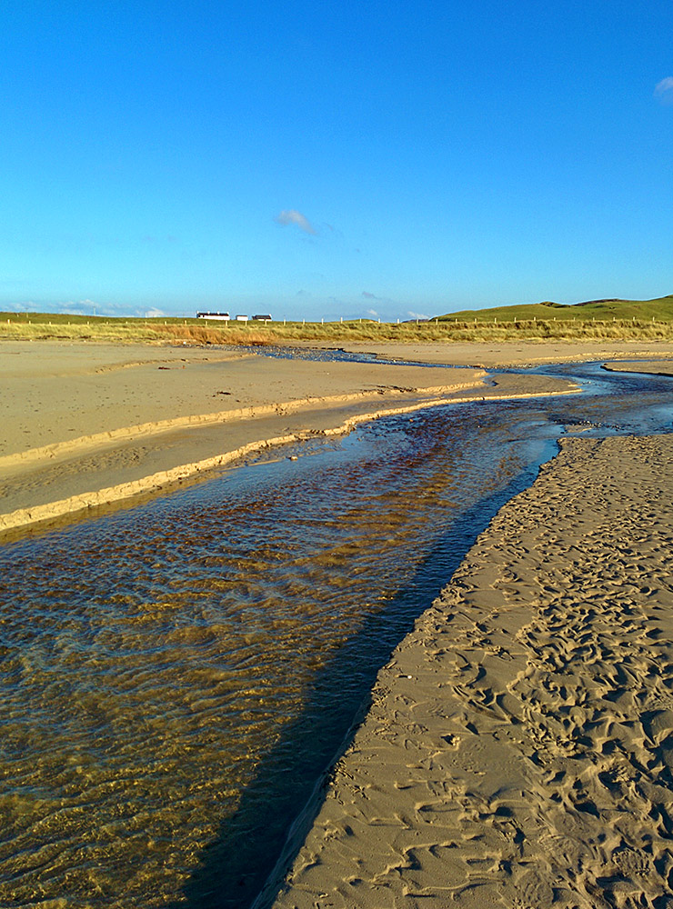 Picture of two burns (streams) merging and crossing a beach