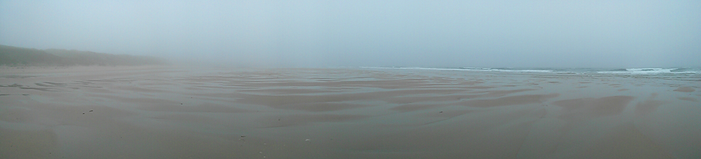 Panoramic picture of a foggy morning on a wide sandy beach