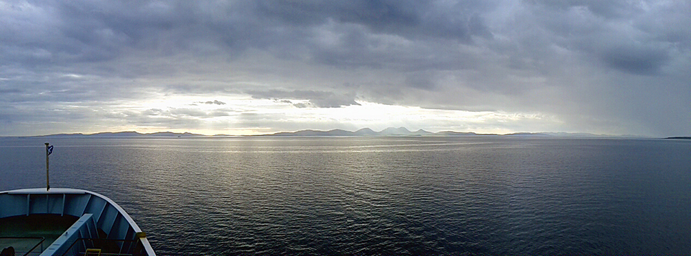 Panoramic picture of two islands on the horizon, seen from a ferry
