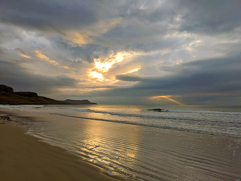 Picture of a cloudy November afternoon on a beach with some bright spots in the clouds and a lone ray of sunshine on the horizon