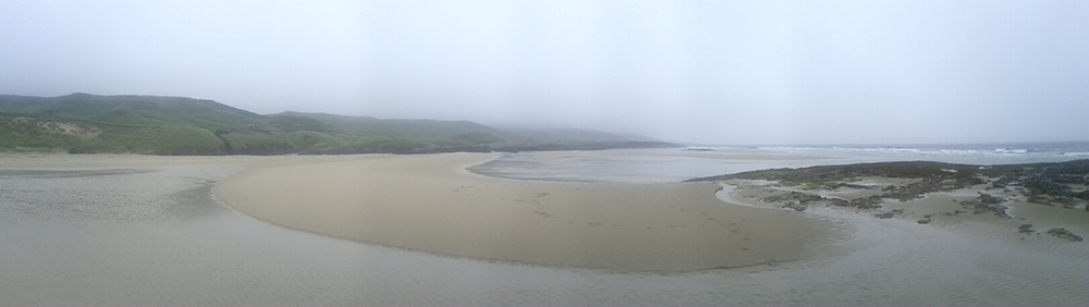 Panoramic picture of a misty June morning at the end of a sandy beach