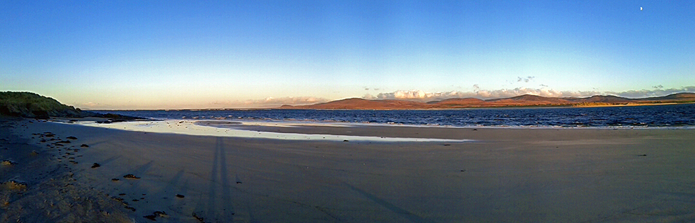 Panoramic picture of a view over a sea loch from a beach in the November afternoon sun
