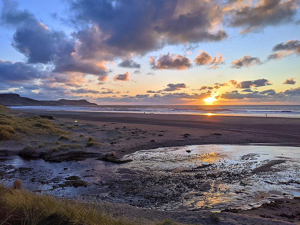 Picture a November sunset over a wide bay with a sandy beach