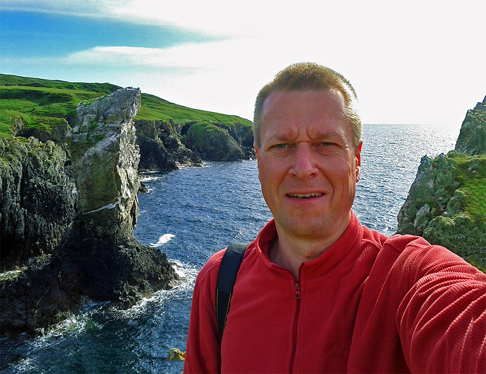 Selfie of a man in front of a sea stack