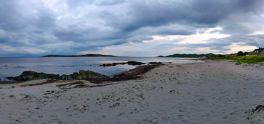 Panoramic picture of a small beach along a bay with a few small island on an overcast summer evening