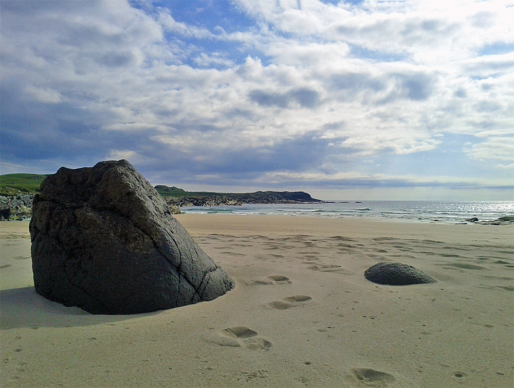 Picture of a big smooth rock on a sandy beach under a partially cloudy sky with bright breaks