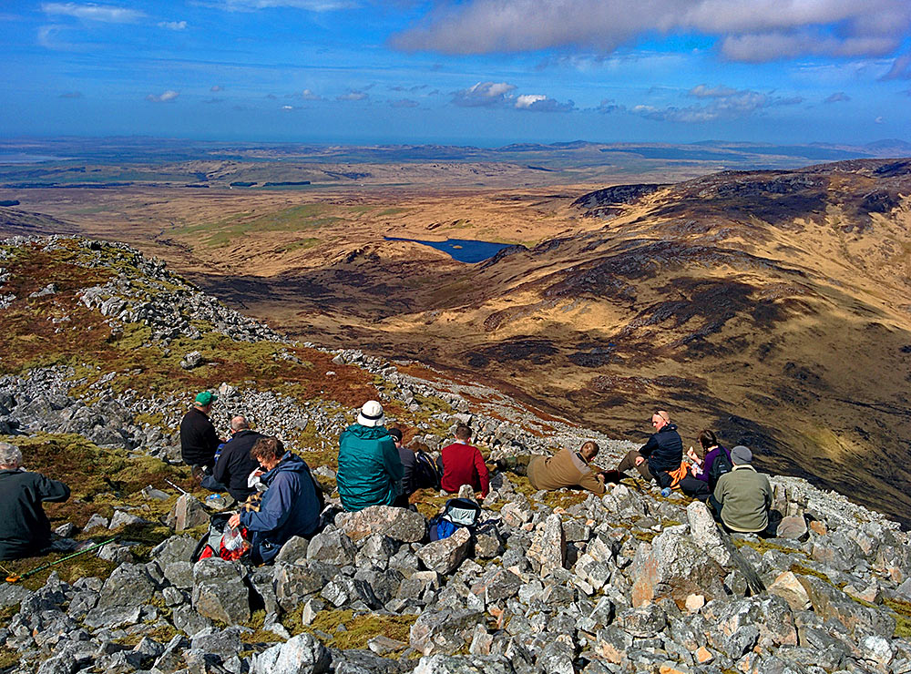 Picture of a group of walkers having lunch on a high hill with scree, a wide view into the distance