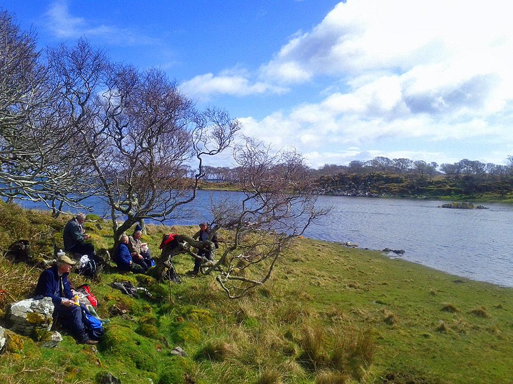 Picture of a group of walkers having lunch near a shore