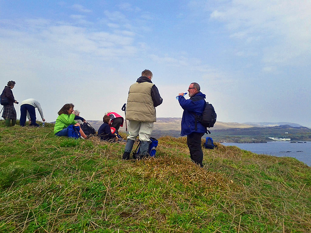 Picture of a group of walkers having lunch on a hill on a small island, a bigger island with a distillery in the background