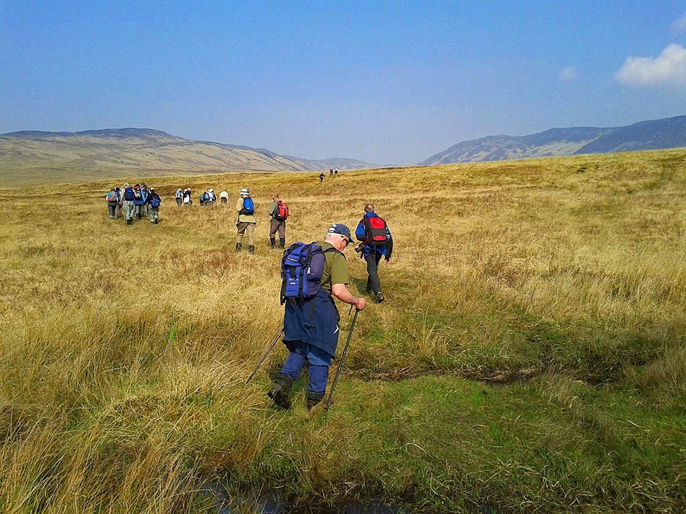 Picture of a group of walkers walking out into the hills