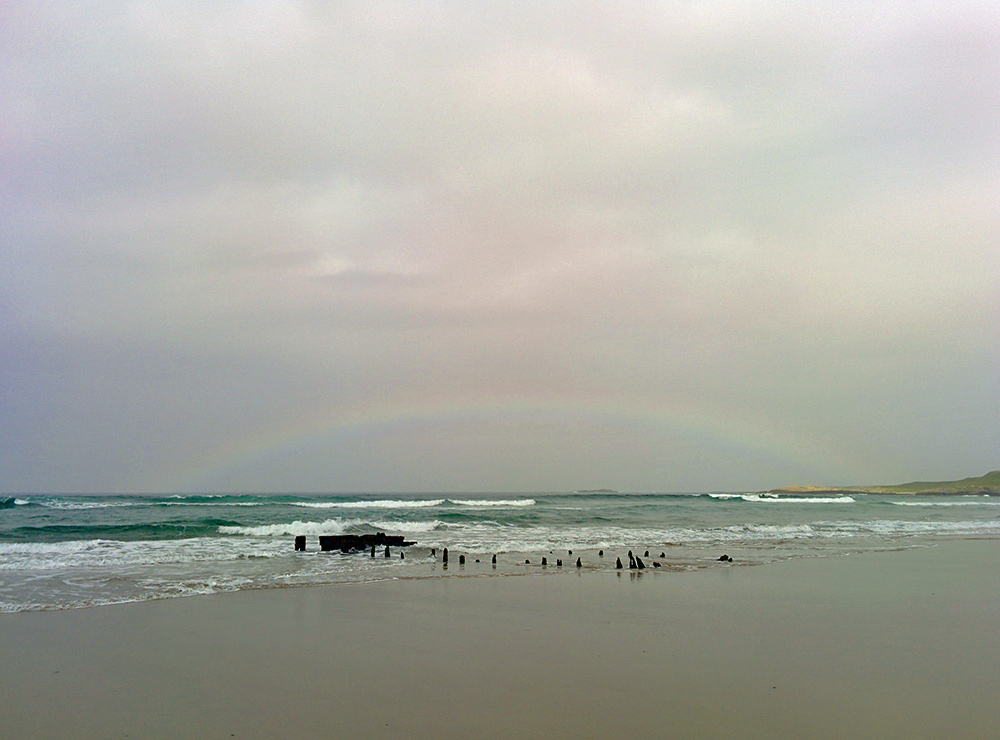 Picture of a faint low rainbow over the wreck of a ship on a beach